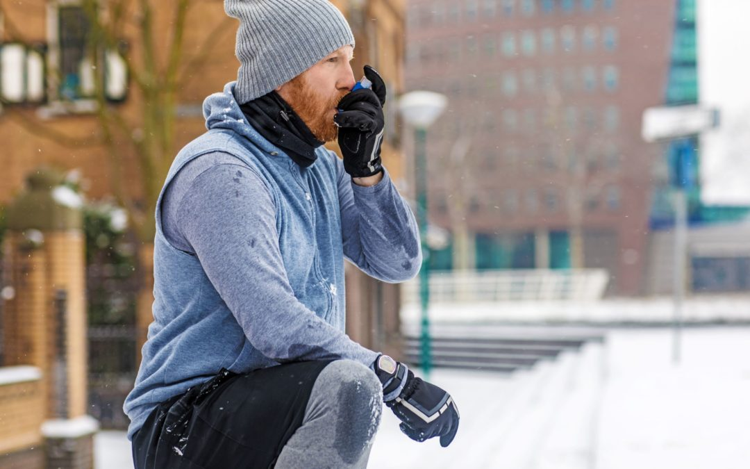 A man stops to use his inhaler while jogging outdoors in the winter. Cold air can be challenging for someone with asthma. It's necessary to take extra precautions in order to prevent asthma attacks in the winter,