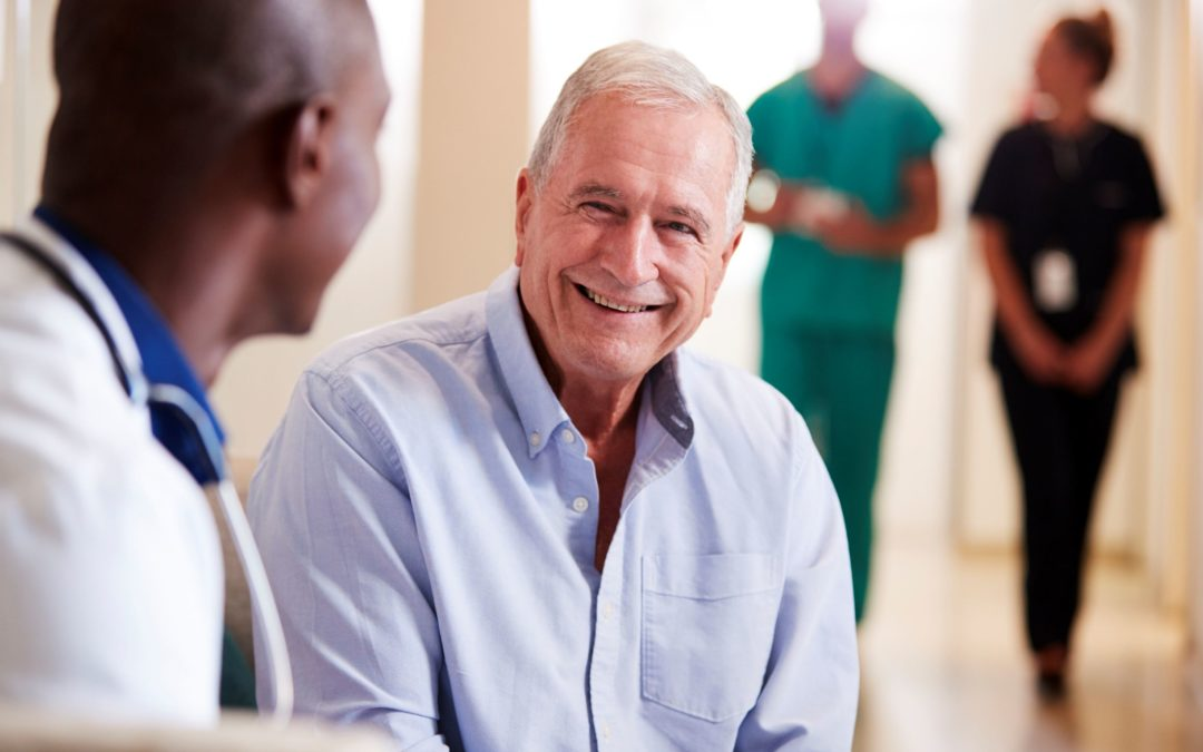 A hospitalist creates a short-term relationship with patients in hospitals. In this image, an adult male patient is smiling as he is speaking with a doctor.