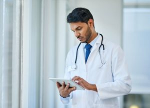A hospital care physician looks at the overall picture and communicates with hospital staff, nurses, patients, and their families in order to optimize a patient's overall care. In this image, a male doctor is standing in hallway while using a digital tablet.