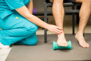 A physical therapists assists a patient in using a foot roller to treat plantar fasciitis. A cold water bottle may also be used in this way to treat the heel pain.